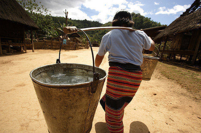 a woman carrying heavy buckets filled with water