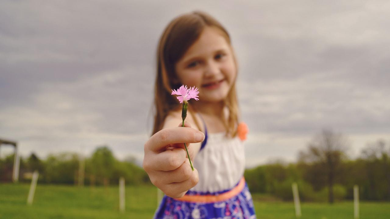 a girl holding a little pink flower