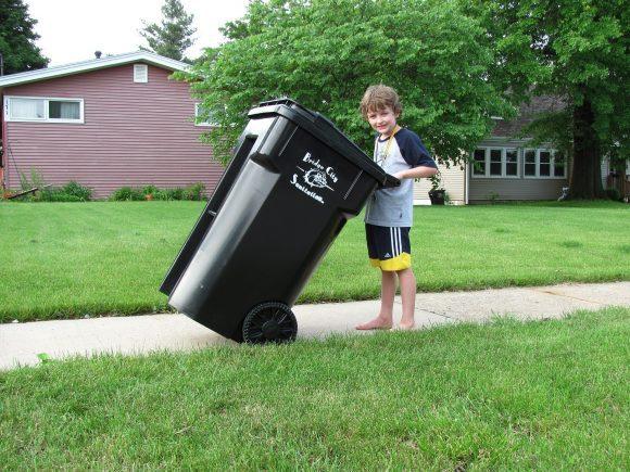 a boy holding recycling bin